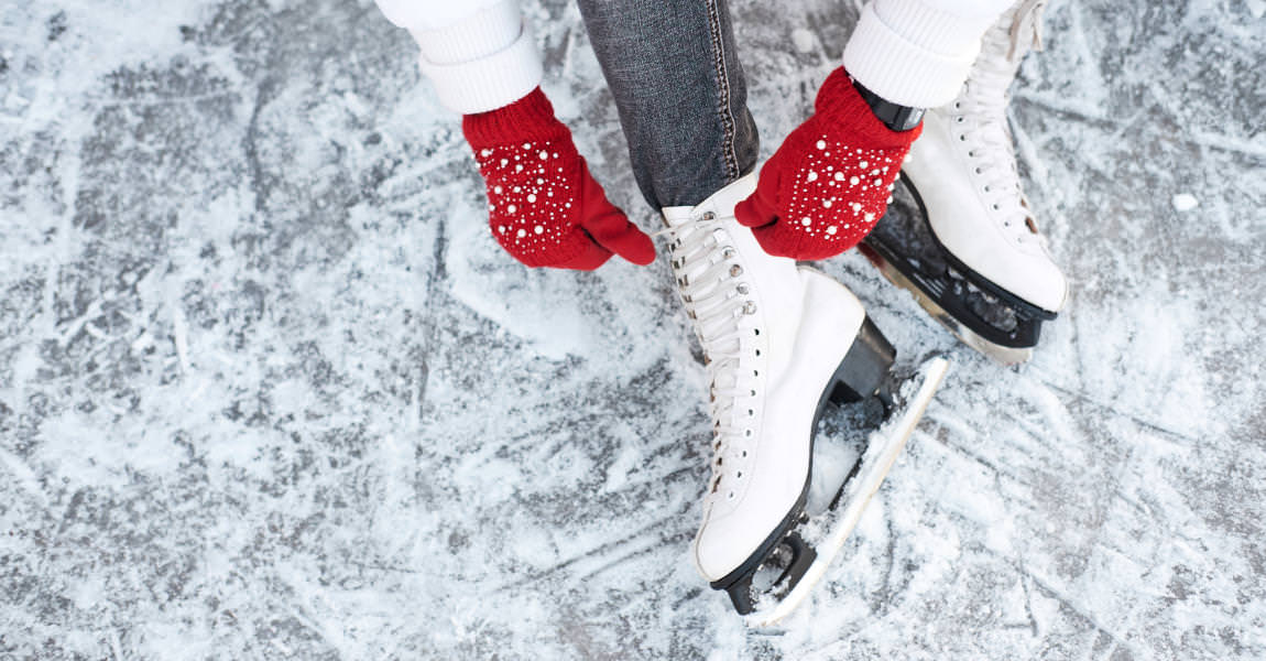 Girl tying shoelaces on ice skates before skating on the ice rink
