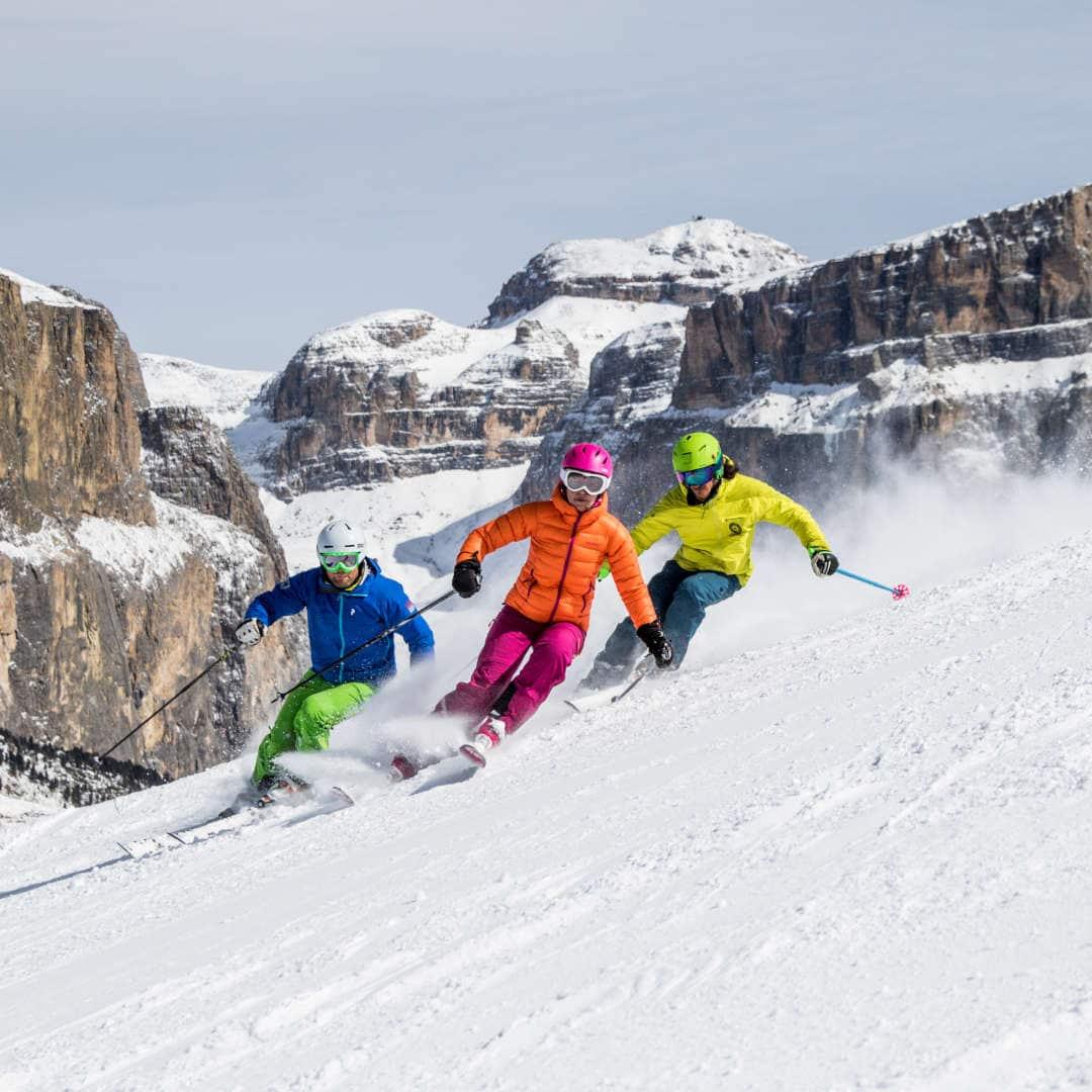 sciatori su pista innevata sulle dolomiti
